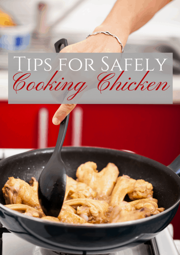 Woman's hand safely cooking chicken in a black frying pan.