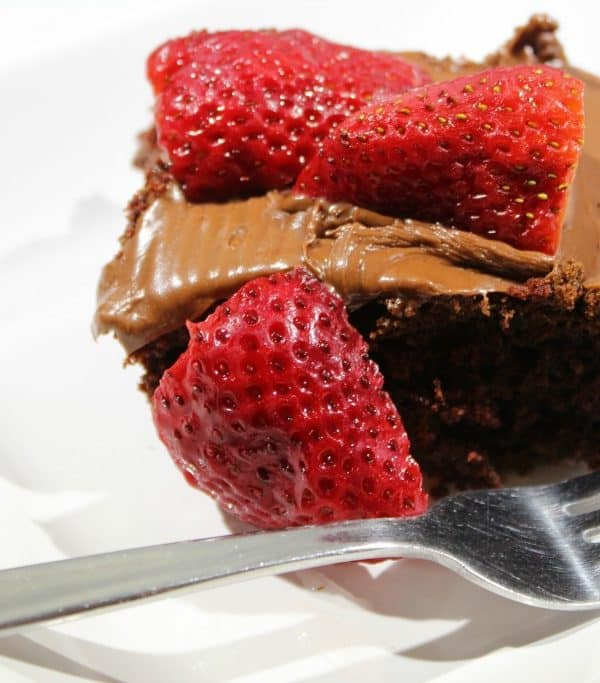 Slice of Thunder Cake with chocolate frosting and strawberry slices on a white plate with a silver fork