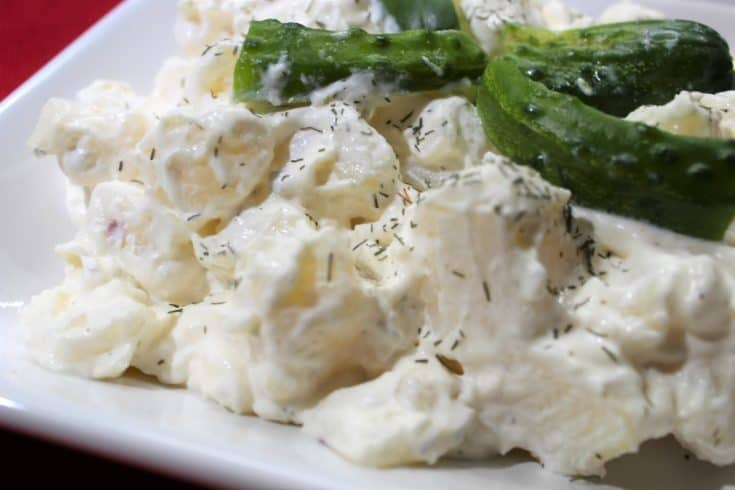 Sour cream and dill potato salad on a white plate garnished with homemade dill pickle and dried dill