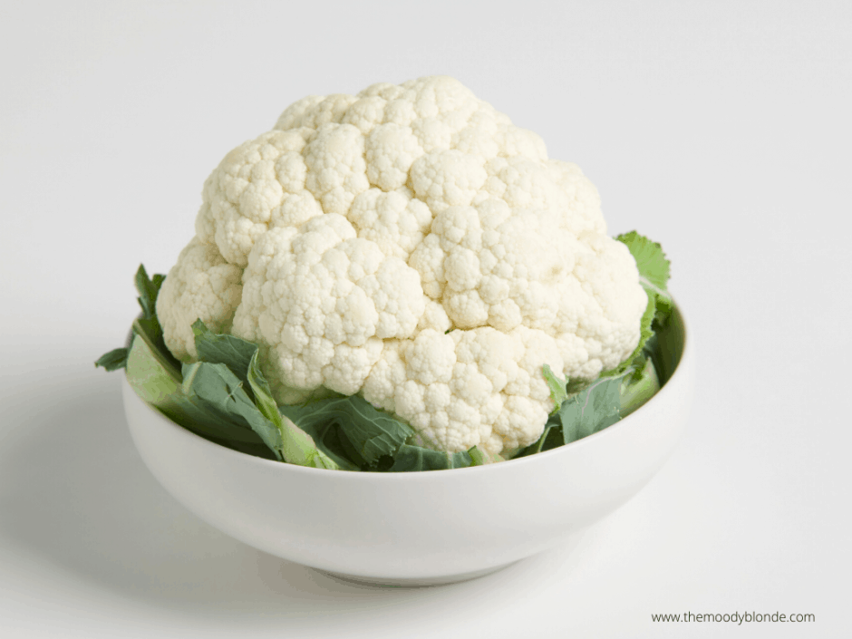 Head of white cauliflower with green leaves in a white bowl on a white background ready to be cut for roasted cauliflower steak recipe
