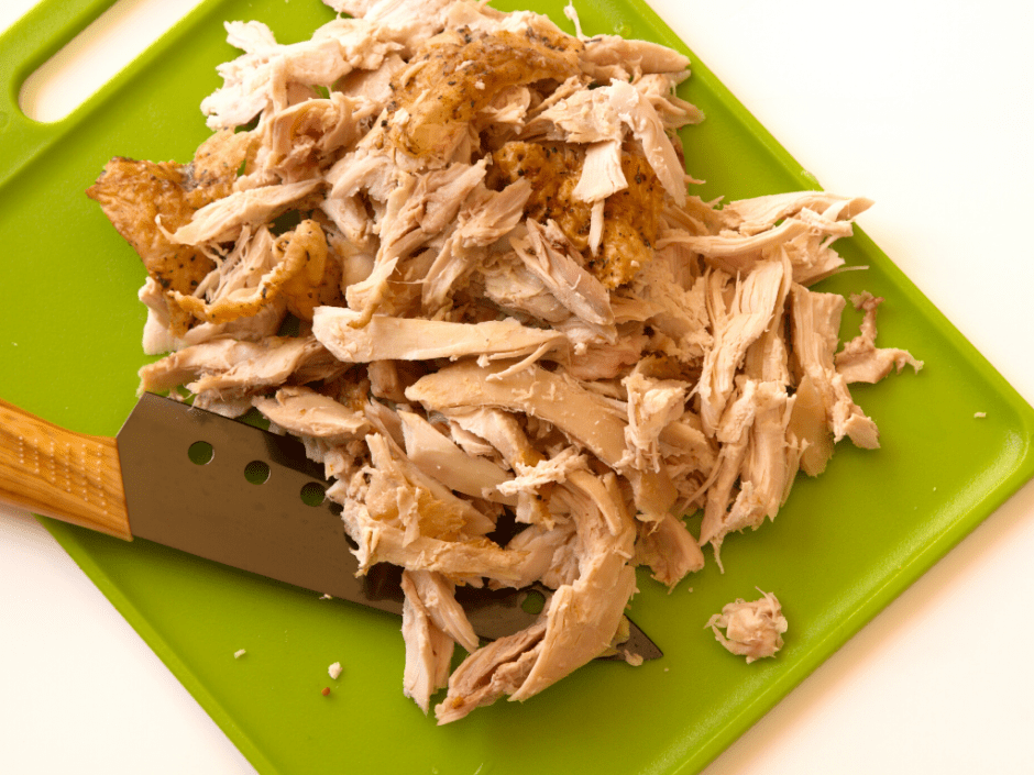 Slow cooker shredded chicken with a knife spread out on a green cutting board